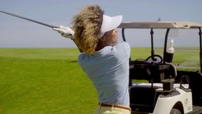 Woman golfer preparing to play a stroke. With a golf cart parked on the fairway just behind her closeup three quarter pose stock video footage