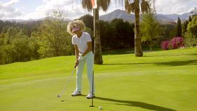 Woman golfer putting for the hole stock video