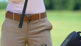 Woman golfer putting on special glove and choosing iron club in golf bag. Stock footage stock video