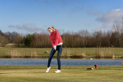 Woman golfer striking the golf ball Stock Photography