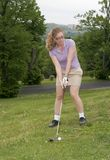 Woman golfer swinging Royalty Free Stock Photo