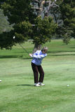 Woman golfer teeing off Stock Photography