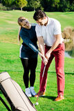 Woman golfer training man to play golf Royalty Free Stock Photography