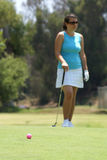Woman Golfing. Woman holding a golf club on a golf course with a pink golf ball in the foreground waiting for her turn to putt Stock Photography