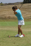 Woman Golfing. Woman swinging a golf club at a pink golf ball on a golf course Stock Images