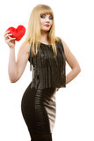 Woman gorgeous girl holding red heart love symbol. Woman elegant blonde long hair girl dark makeup red lipstick black evening dress holding red heart love symbol stock photography
