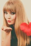 Woman gorgeous girl holding red heart love symbol. Woman elegant blonde long hair girl dark makeup red lipstick holding red heart love symbol flirting, sending Stock Images