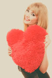 Woman gorgeous girl holding red heart love symbol. Woman elegant blonde long hair girl dark makeup red lipstick holding red heart love symbol flirting, studio stock photography
