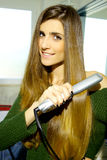 Woman with gorgeous long hair straightening in bathroom Royalty Free Stock Photos