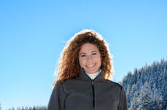 Woman with a gorgeous smile backlit by the sun. Attractive woman with a gorgeous smile and wavy long hair backlit by the sun standing outdoors in winter looking Stock Photography