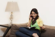 Woman gossiping on mobile phone and reading a magazine Royalty Free Stock Photo