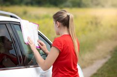 Young woman got lost on the deserted road looking in map for path. Woman got lost on the deserted road looking in map for path Royalty Free Stock Photos