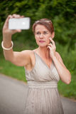 Woman in Gown Taking Self Portrait with Cell Phone Royalty Free Stock Photography