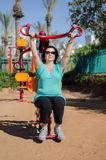 Woman grabbing the bar of Lat Pull machine. Mature woman grabbing the bar of Lat Pull machine in outdoor fitness circuit Royalty Free Stock Images