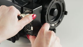 Woman Grabbing Black Cable Plugged to Video Camera. Cable plugging. Close-up. Shot on RED Epic stock video footage