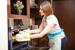 Woman grabbing a cake with oven mitts Royalty Free Stock Photo