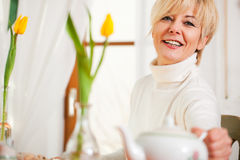 Woman grabbing coffee or tea pot Stock Photography