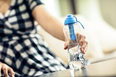 Free Woman Grabs The Bottle Of Filtered Water Stock Image - 186859571