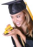 Woman Graduate. A pretty woman graduate holding a school bus royalty free stock photos