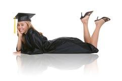 Woman Graduate. A beautiful woman graduate laying on a white background stock photos