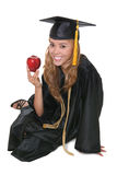 Woman Graduate. A beautiful woman graduate with an apple over white royalty free stock photography