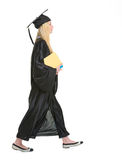 Woman in graduation gown with books going sideways Royalty Free Stock Photos