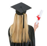 Woman in graduation gown with diploma . rear view Royalty Free Stock Photography