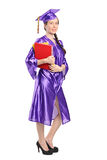 Woman in graduation gown holding books Stock Photo