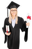 Woman in graduation gown holding diploma and books Stock Photo