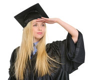 Woman in graduation gown looking into distance Stock Image