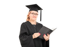 Woman in graduation gown reading a book Stock Photography