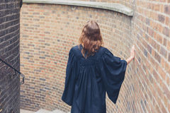 Woman in graduation gown on stairs Royalty Free Stock Photos