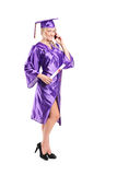 Woman in graduation gown talking on the phone Stock Photo