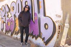 Woman at the graffiti brick wall Royalty Free Stock Image