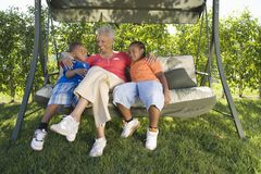 Woman With Grandchildren Sitting On Swing Chair Royalty Free Stock Images