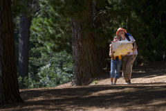 Woman and granddaughter standing in woods looking at map Stock Photo