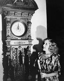 Woman with grandfather clock at midnight Royalty Free Stock Photo