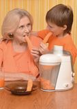 Woman and grandson eating carrots Stock Image