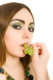 Woman with grape in her mouth Royalty Free Stock Image
