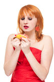 Woman with grapefruit isolated. Attractive woman looking at grapefruit, red lips and dress Royalty Free Stock Photography