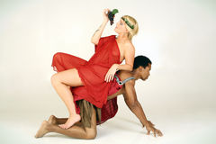 Woman with Grapes. A theatrical looking blonde woman eating grapes while sitting on the back of a black man Stock Images