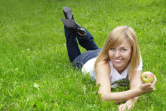 Woman on the grass. Beautiful young woman on the grass with apple royalty free stock image