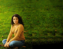 Woman and Grass. Woman sitting on green grass with lots of copy space Stock Images