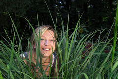 Woman in the grass. Blonde woman looking through the grass Royalty Free Stock Photo