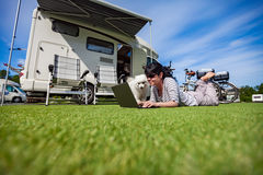 Woman on the grass with a dog looking at a laptop Stock Images