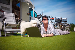 Woman on the grass with a dog looking at a laptop Stock Photo