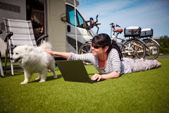 Woman on the grass with a dog looking at a laptop Royalty Free Stock Photos
