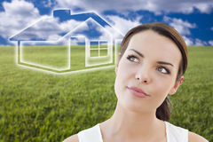 Woman and Grass Field with Ghosted House Figure Behind Royalty Free Stock Photo