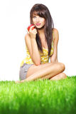Woman on grass holding apple. Royalty Free Stock Photography