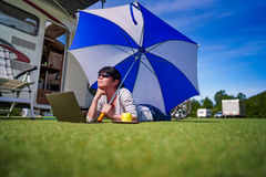 Woman on the grass, looking at the laptop under umbrella near th Royalty Free Stock Photography